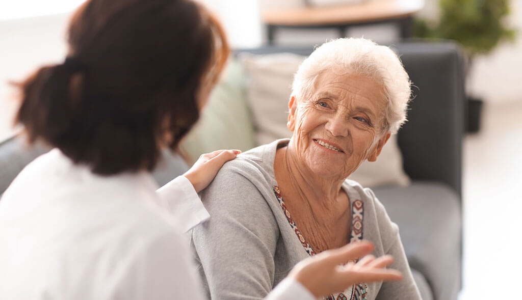Home health aide talks with elderly woman.