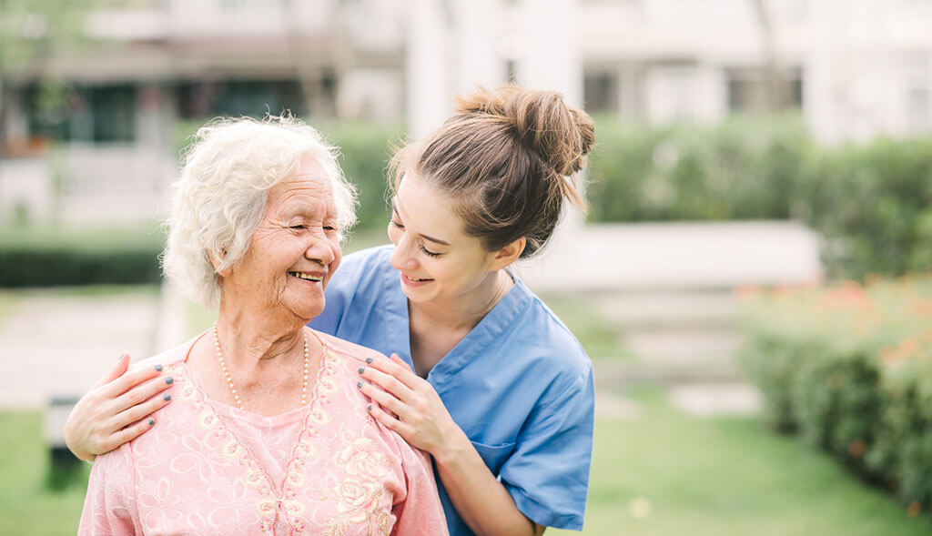 Home healthcare worker assists older woman.