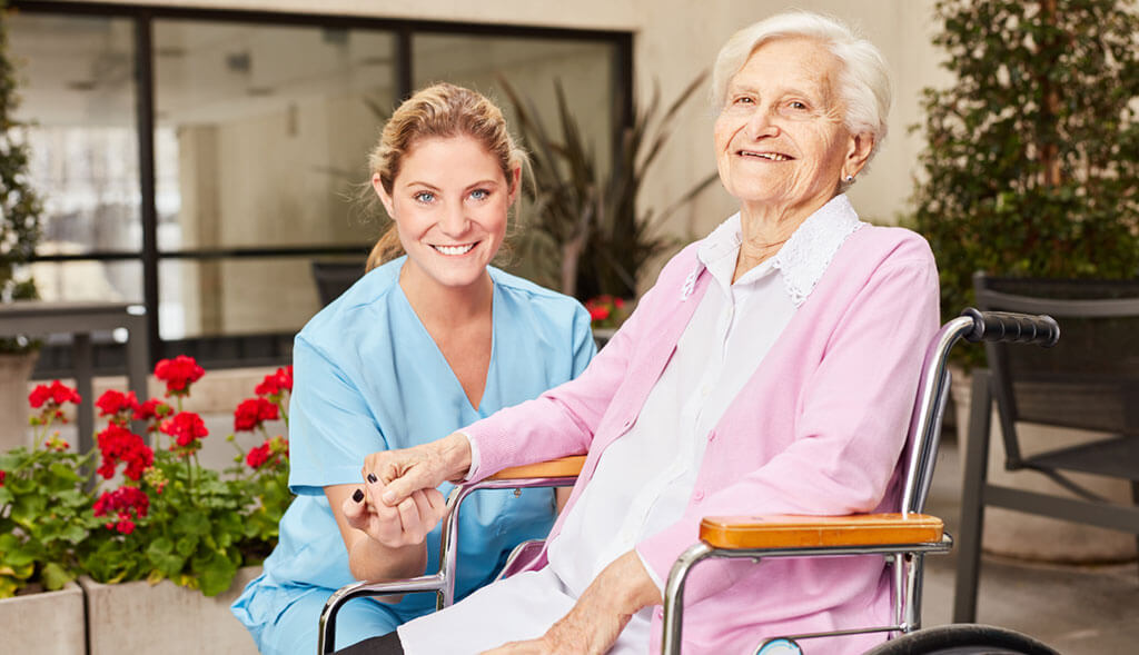 Home healthcare worker holds hands with elderly woman in wheelchair.