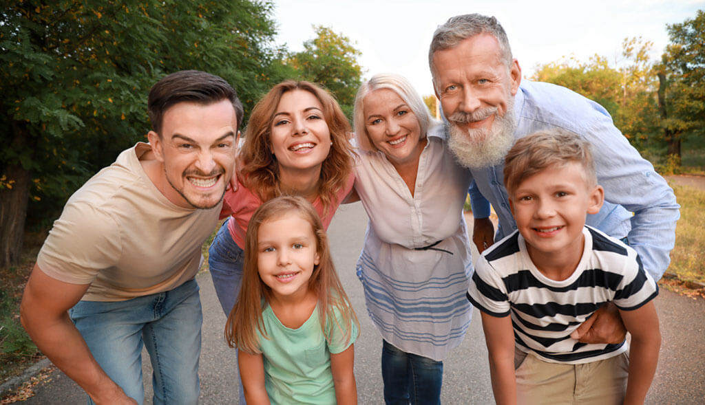 Multi-generational family enjoys time together outside on a walk.