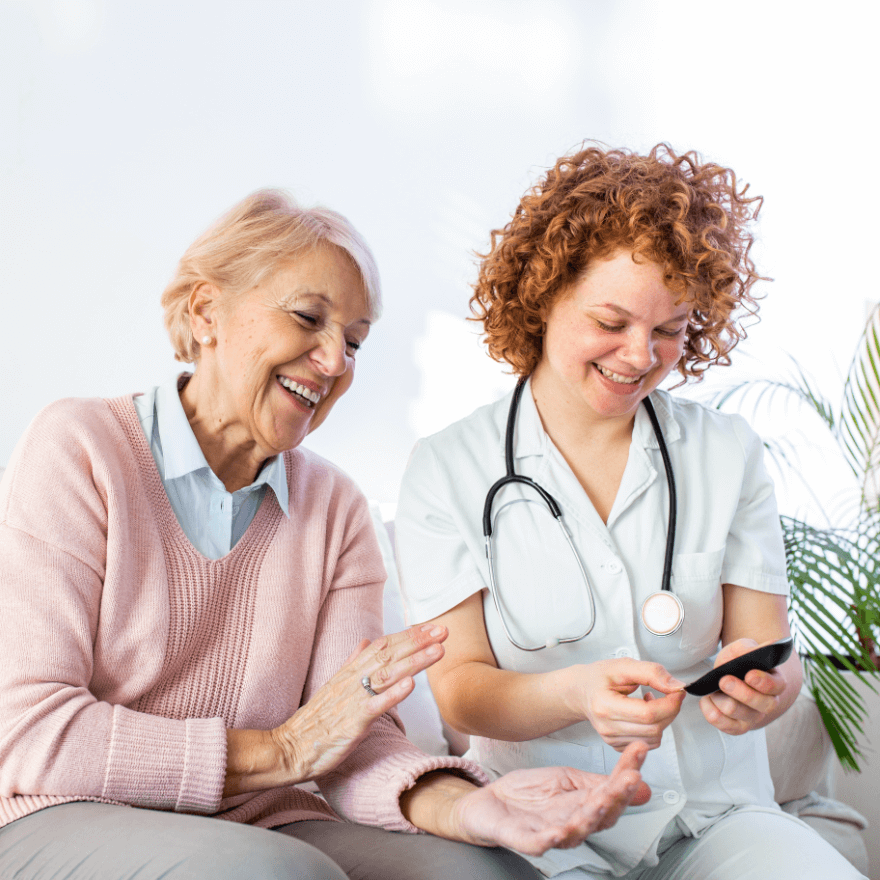 Home healthcare worker chats with older woman.
