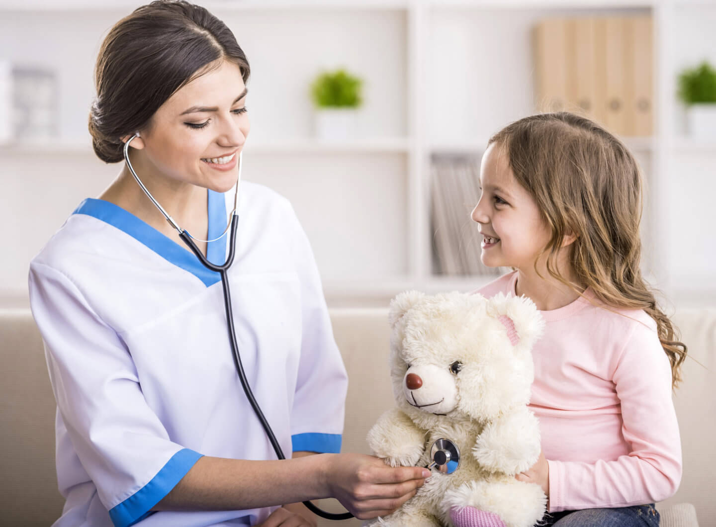 Home healthcare worker uses stethoscope on child's teddy bear.