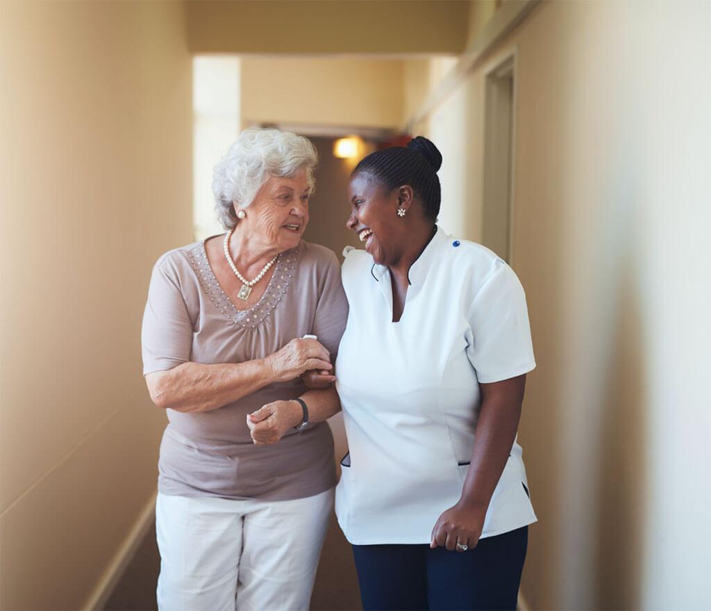 Home healthcare worker helps elderly woman walk down hallway.