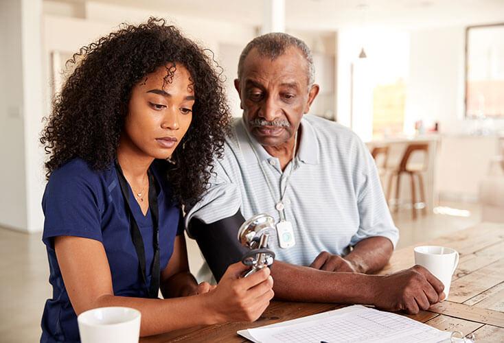 Home healthcare worker takes elderly man's blood pressure.