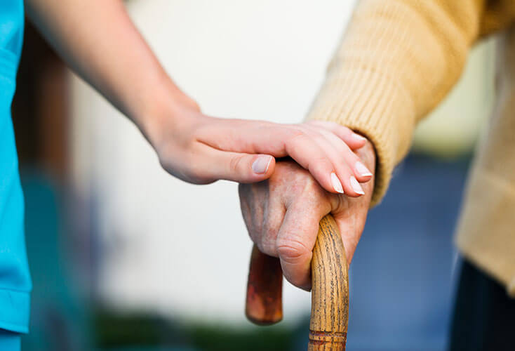 Home healthcare worker holds the hand of elderly person using a cane.